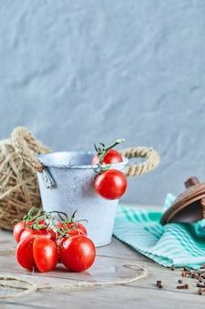 Secchio di pomodori e pomodoro tagliato a metà sulla tavola di legno