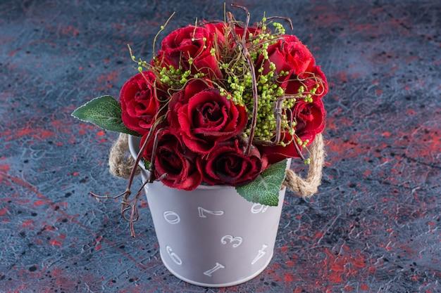 Un secchio con bouquet di bellissime rose rosse su fondo marmo.