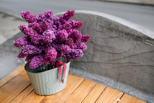Bucket with a bunch of purple lilac flowers on a wooden bench