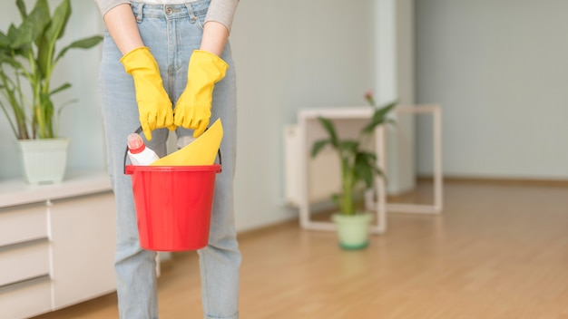 Ведро с чистящими средствами, которое держит женщина в перчатках