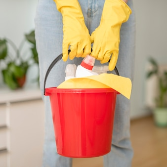 Bucket with cleaning supplies held by woman