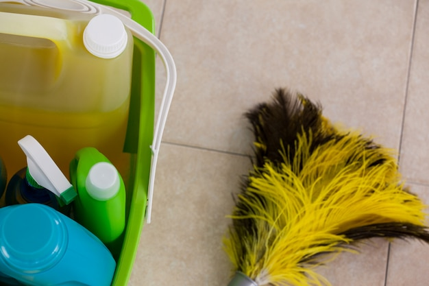Bucket with cleaning supplies and mop on tile floor