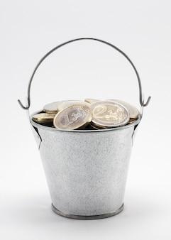 Ведро с монетами, изолированными на белом, с обтравочным контуром