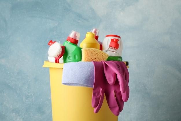 Ведро с моющими и чистящими средствами на синем фоне, крупным планом