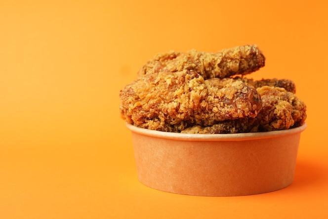 secchio con pollo fritto su sfondo arancione