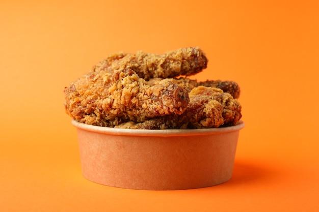 Bucket with fried chicken on orange background