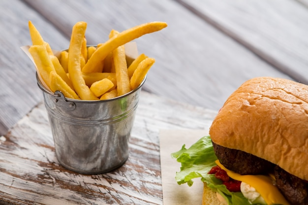 감자 튀김과 버거가 든 양동이. 구운 고기와 롤빵. 카페에서 미국식 식사. 비프버거의 베스트 레시피.