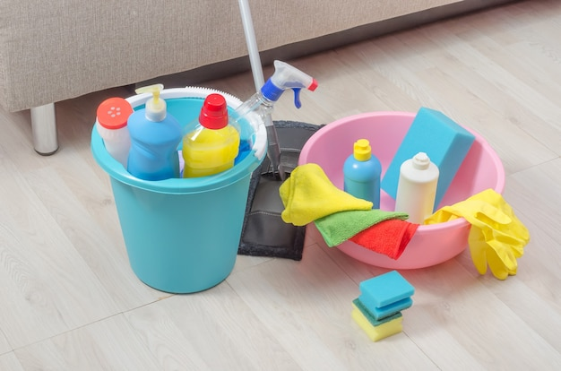 바닥에 냅킨, 스폰지 및 장갑이 달린 다양한 청소 제품이 담긴 양동이.