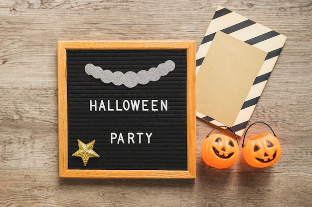 Buckets and halloween greeting card near frame with writing