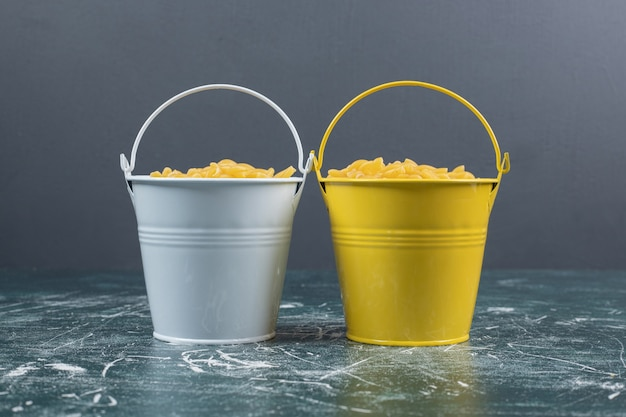 Buckets of raw spiral pasta on blue background. high quality photo