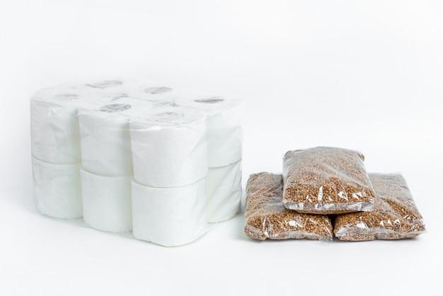 ソバとトイレットペーパーの包装。孤立した白地の寄付キット。検疫隔離期間中の必須商品の危機防止在庫。