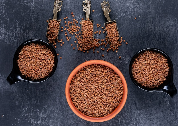 Buckwheat in a bowl and black cups and shovels top view on a dark