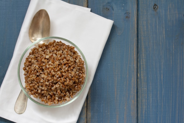 Buckwheat in bowl with spoon on blue wooden surface