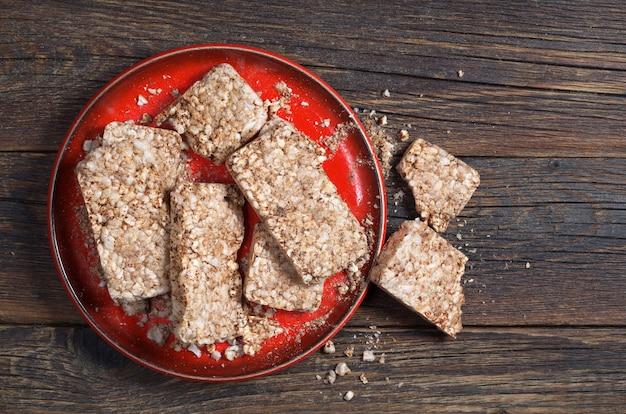 赤いプレートの木製の背景、上面図のそばのぱりっとしたパン。ダイエットクッキー