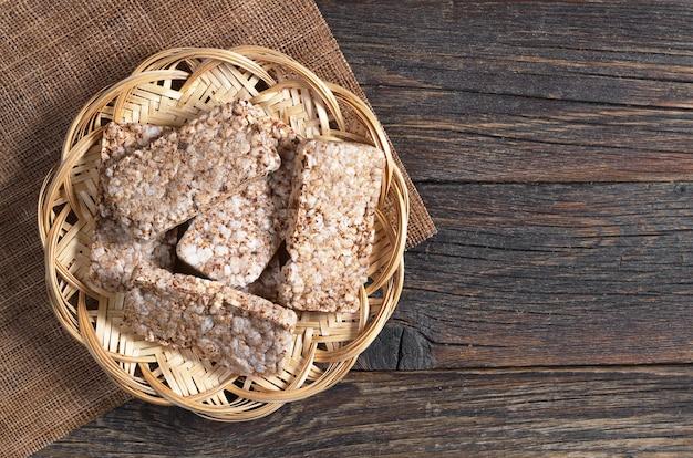 暗い木製のテーブル、上面図の籐のプレートでソバのパリパリしたパン。ダイエットクッキー