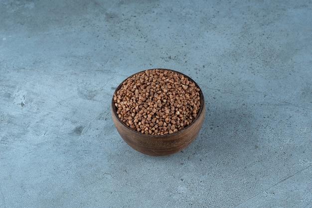 Гречневая крупа в деревянной чашке на синем фоне. фото высокого качества
