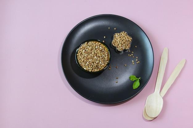 검은 접시에 메밀 곡물과 그릇 분홍색 배경에 메밀 글루텐 무료 곡물
