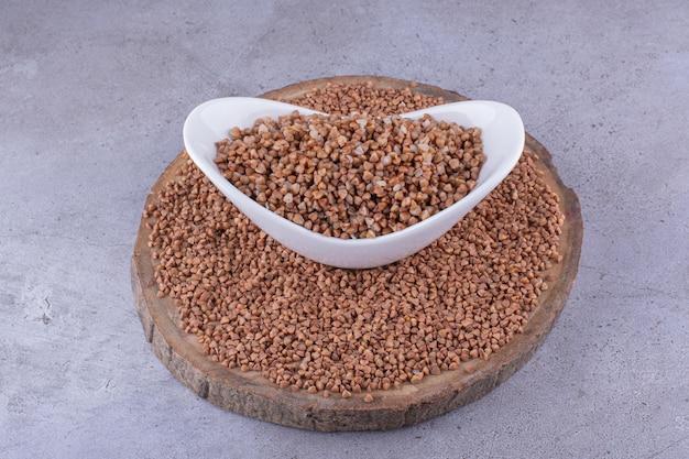 Гречневая крупа разложена на деревянной доске вокруг миски с вареной гречкой на мраморном фоне. фото высокого качества