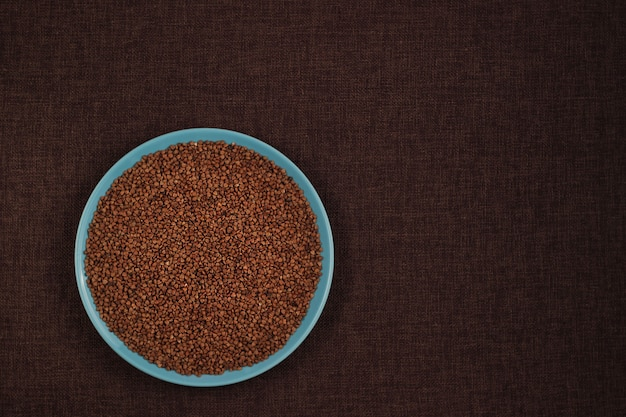 Buckwheat groats in a blue bowl and brown linen background with copy space for recipe