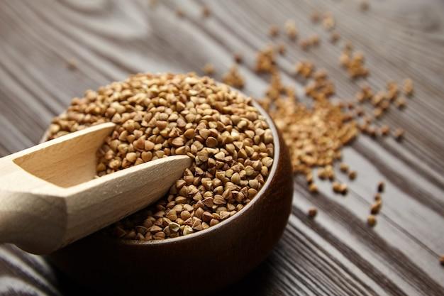 ボウル、木製スクープ、クローズアップのそば粉(殻付き種子)