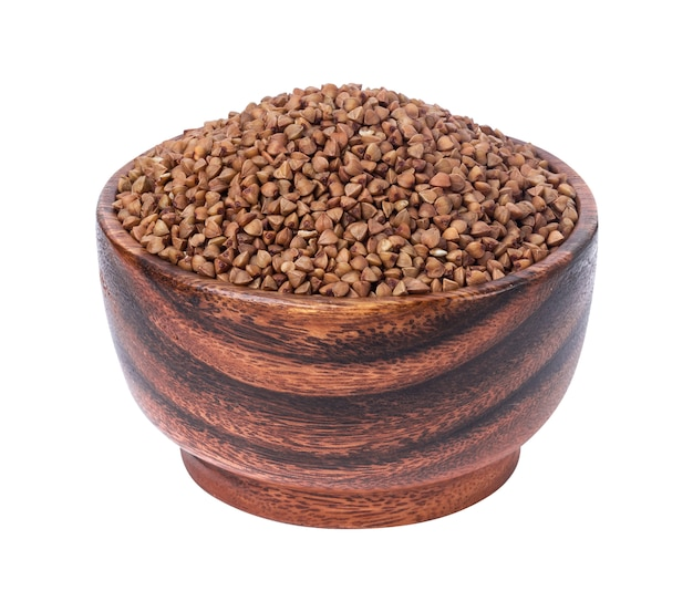 Buckwheat groats in wooden bowl isolated on white
