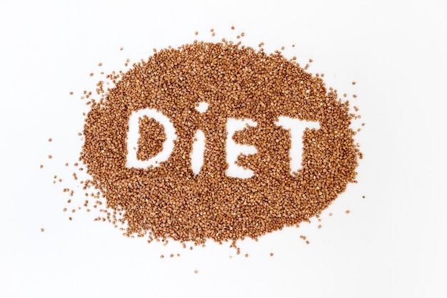 Buckwheat lettering diet. texture from raw buckwheat grains. healthy food concept.