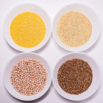 Buckwheat, millet, rice and peas on a white table. the view from the top.