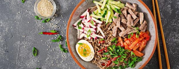 牛肉、卵、野菜のそば。韓国料理。そばパスタスープ。上面図。平干し。バナー
