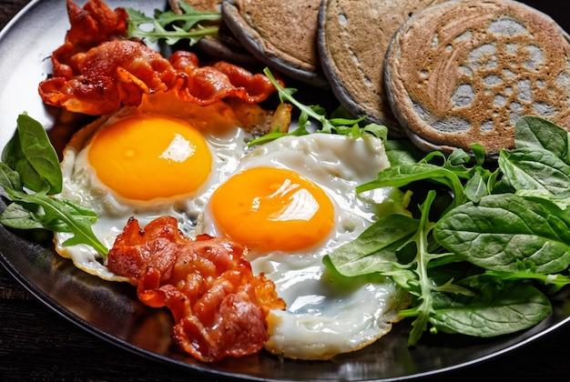 日当たりの良い目玉焼き、ベーコンの炒め物、グリーンサラダを添えたそばパンケーキを木製のテーブルの黒いプレートで提供、朝の朝食、上からの水平方向の眺め、クローズアップ