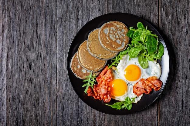 日当たりの良い目玉焼き、揚げベーコン、グリーンサラダを添えたそばパンケーキを木製のテーブルの黒いプレートで提供、朝の朝食、上からの水平方向の眺め、フラットレイ、空きスペース