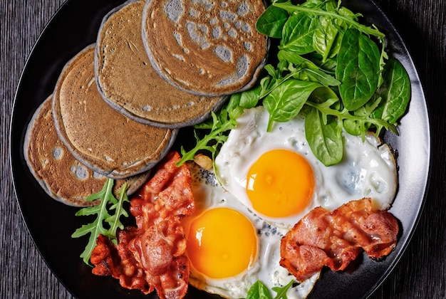 日当たりの良い目玉焼き、ベーコンの炒め物、グリーンサラダを添えたそば粉のパンケーキを木製のテーブルの黒いプレートで提供、朝の朝食、上からの水平方向の眺め、マクロ