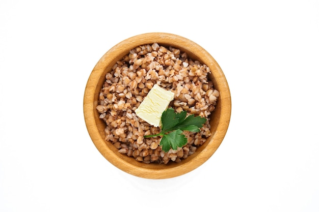 Buckwheat porridge in bamboo bowl with parsley leaf and butter isolated in white. gluten-free ancient grain for healthy diet