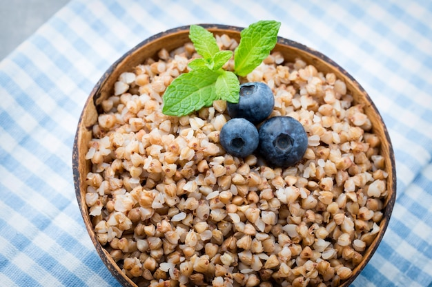 Buckwheat porridge in a bowl with mint leaves and blueberries