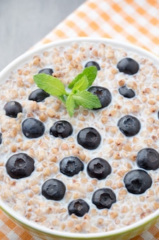 Buckwheat porridge in a bowl with mint leaves and blueberries.