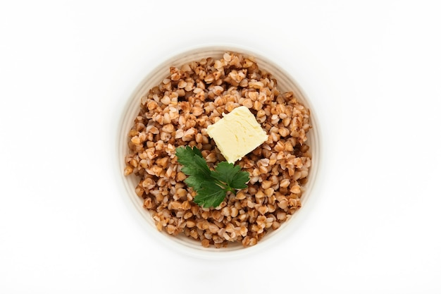 Buckwheat porridge in bowl with parsley leaf and butter isolated in white. gluten-free ancient grain for healthy diet