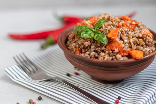 Buckwheat porridge in a bowl with stewed carrots. decorated with green leaves.