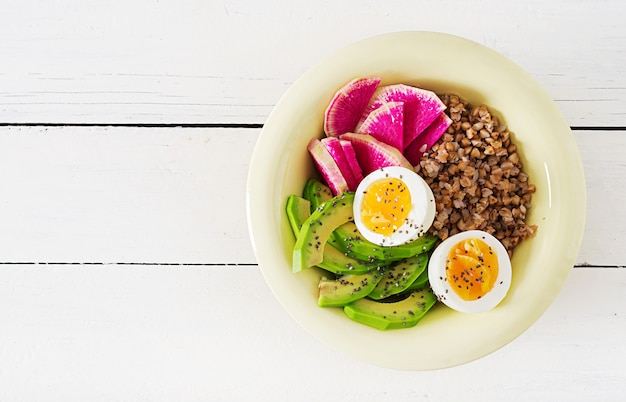 Buckwheat porridge buddha bowls with avocado, boiled eggs and  watermelon radish on white table. healthy breakfast. top view