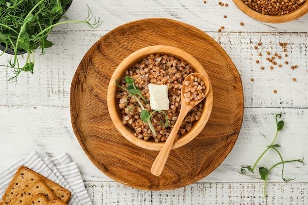 오래된 흰색 나무 배경에 파슬리 잎과 버터를 넣은 그릇에 메밀 죽. 가정식. 건강한 식단을 위한 글루텐 프리 고대 곡물. 평면도. 공간을 복사합니다.