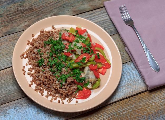 野菜、トマト、ピーマン、タマネギと焼いた魚の青いwhitingの飾りとそば米雑炊