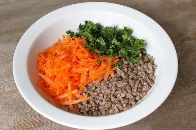 すりおろしたにんじんとパセリを木製のテーブルに白いプレートに入れたそばのお粥。健康的な食事、ダイエット、無駄のない食品の概念。閉じる。セレクティブフォーカス。コピースペース