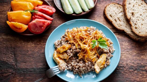 나무 배경에 고기, 양파, 당근을 넣은 메밀 죽. 신선한 야채, 오이, 토마토와 함께.
