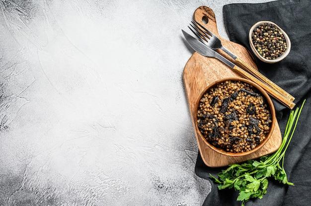 Гречневая каша с грибами. веганская еда. русская, украинская кухня. серый фон