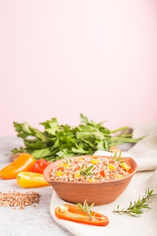 グレーとピンクの壁とリネン織物の粘土ボウルに野菜とそば米のおridge。側面図、コピースペース、セレクティブフォーカス。