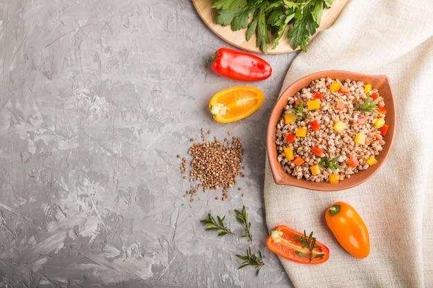 灰色のコンクリート背景とリネン織物の粘土ボウルに野菜とそば米雑炊。トップビュー、コピースペース。