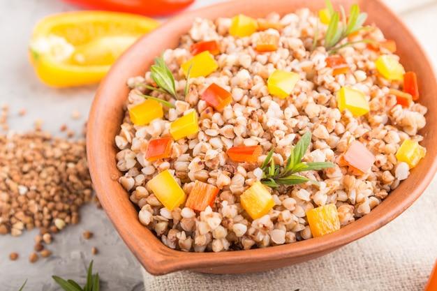 灰色のコンクリート表面とリネン織物の粘土ボウルに野菜とそば米のおpor。サイドビュー、クローズアップ、セレクティブフォーカス。