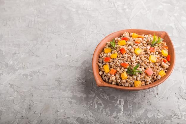 Гречневая каша с овощами в глиняной миске на серой бетонной поверхности. вид сбоку, копия пространства