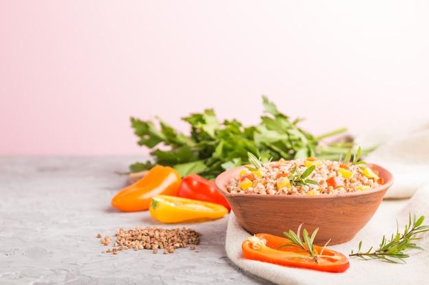 灰色の表面とリネン織物の粘土ボウルに野菜とそば米のおpor。側面図、コピースペース、セレクティブフォーカス。