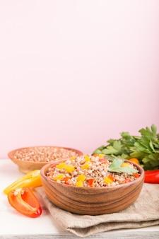 ピンクの背景とリネン織物の木製ボウルに野菜とbuck麦のおridge。側面図、コピースペース、セレクティブフォーカス。