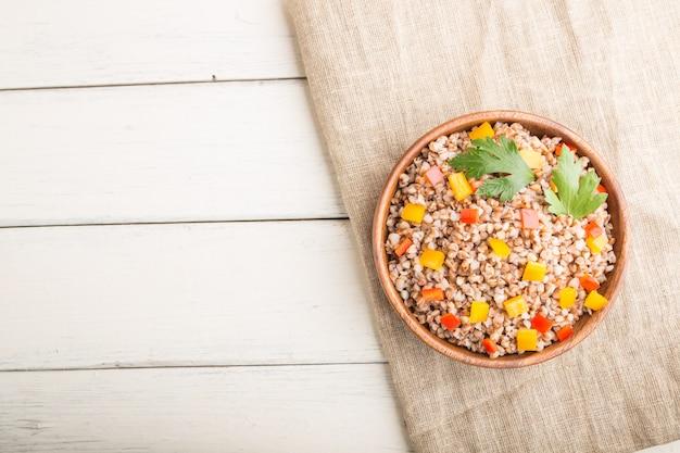 白い木製の背景とリネン織物の木製ボウルに野菜とそば米のおridge。トップビュー、コピースペース。
