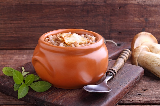 Buckwheat porridge with white mushrooms in a clay bowl on a wooden background